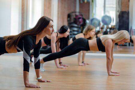 Colocar hermosas mujeres jóvenes haciendo flexiones en el gimnasio moderno