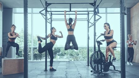 Group of strong active female athletes having training in modern gym,