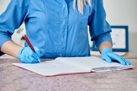 Closeup of young vet doctor writing diagnosis in special folder