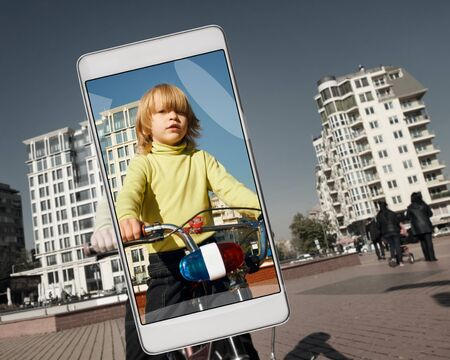 Smartphone displaying photo of little boy riding bike on city street. Original items have been removed from the front panel