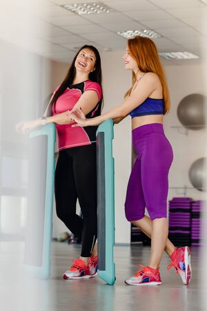 Portrait of two athletic sporty women posing with steppers in modern gym