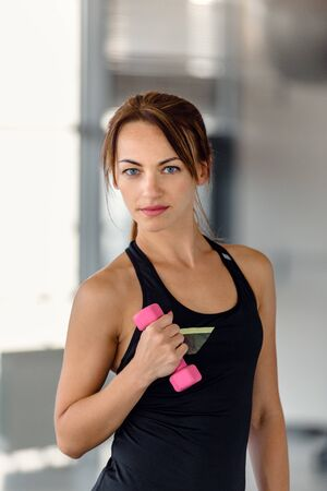 Portrait of beautiful young athletic woman training with dumbbell