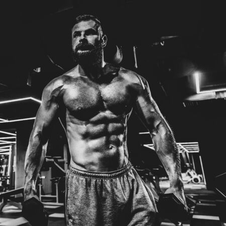 Portrait of strong handsome fit man exercising in gym with dumbbells, dramatic black and white image Reklamní fotografie