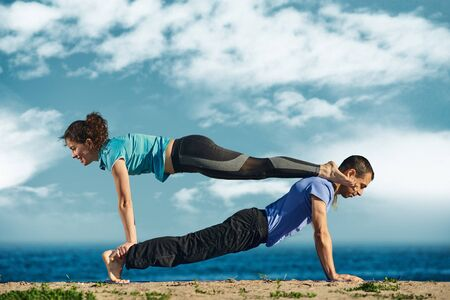 Healthy man and fit young woman training together and doing acroyoga Фото со стока