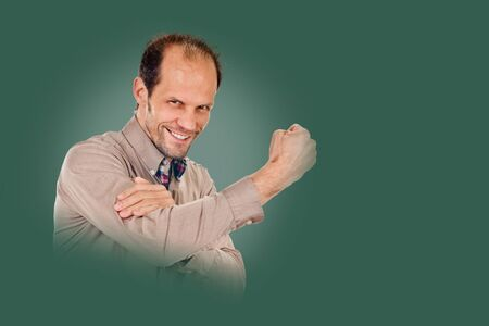 young man showing cubital sign. Synonym sign of middle finger on background pine shade green