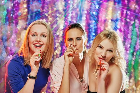 Portrait of three happy pretty girlfriends with carnival whistles celebrating party