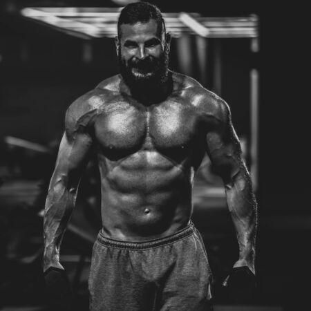 Joven y poderoso hombre en forma haciendo levantamiento de bíceps con pesas, dramática imagen en blanco y negro Foto de archivo