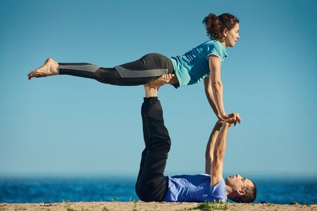 Two young sporty people practicing acro yoga in pair