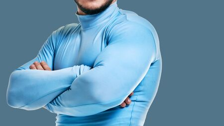 man with crossed hands showing muscles on blue background Reklamní fotografie