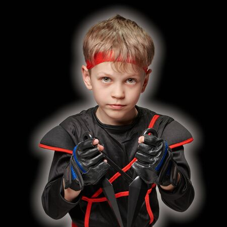 Young boy black ninja costume with kunai posing on black background with light effect Banque d'images