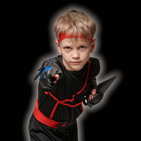 Ninja boy ready to throw kunai for attack on black background Banque d'images