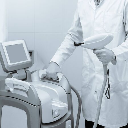 Medical worker in protective glasses setting laser machine before procedure