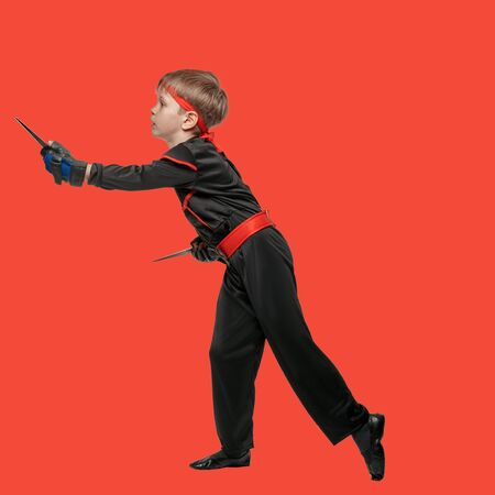 Young boy in ninja uniform practicing knife throwing on red background Stock Photo