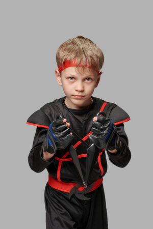 Young boy dressed as ninja posing with kunai on gray background