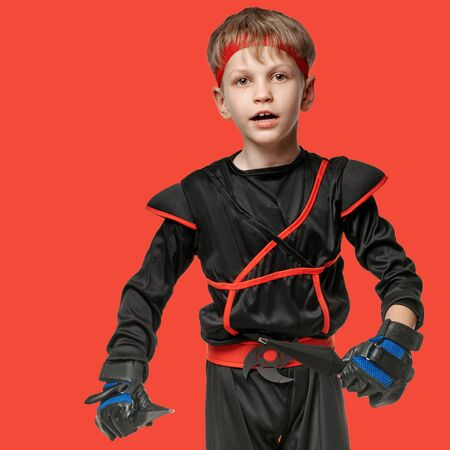 Portrait of healthy active boy exercising with kunai throwing knives on red background Stock Photo