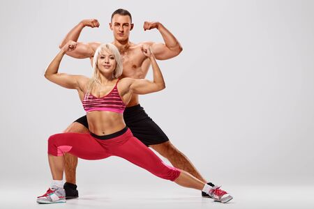 Young sporty couple bodybuilders training together and showing biceps