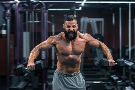 Muskulöser athletischer Bodybuilder, der hart im Fitnessstudio auf dunklem Hintergrund arbeitet