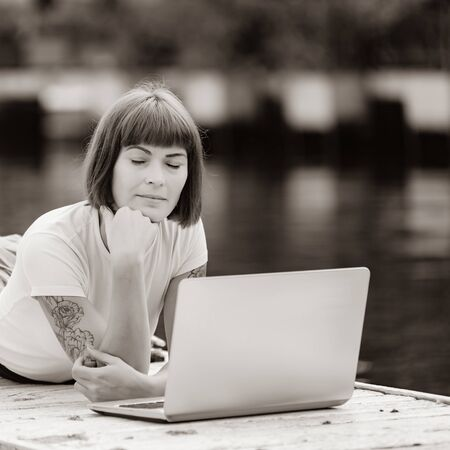 Content writer thinking text on laptop while lying on pier with closed eyes