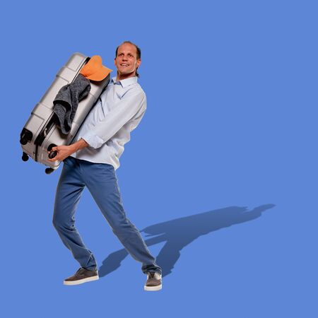 Full portrait of happy man holding suitcase with all necessary clothes for travel on blue cornflower color background