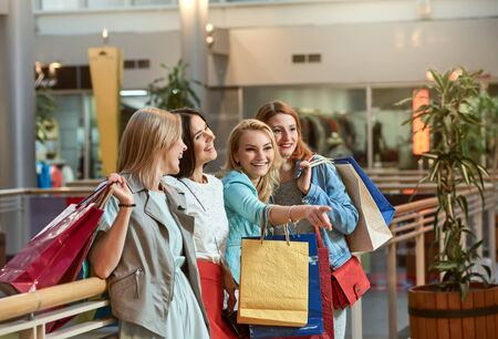 Group of happy girlfriends smiling with a lot of shopping bags Stock Photo