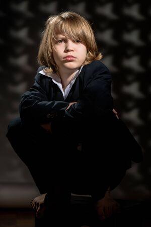 Vintage portrait of young serious boy sitting in black suit Standard-Bild