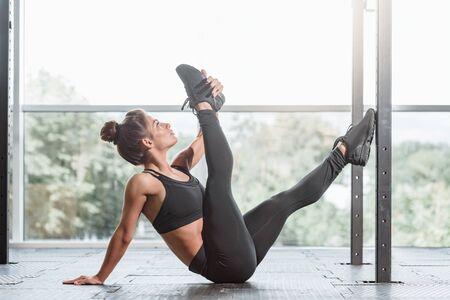 Slim attractive sporty woman doing gymnastics in light gym Фото со стока