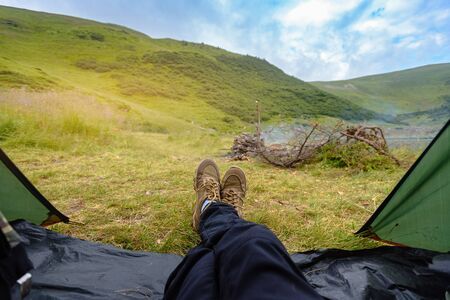 Closeup of male tourist resting in tent after trekking in Carpathian mountains