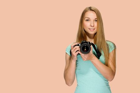 Portrait of attractive smiling girl holding professional photo camera on salmon red background