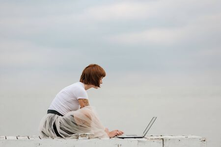 Young woman checking e-mail on laptop computer while sitting on pier
