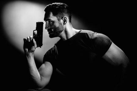 Monochrome portrait of secret agent holding gun on dark background with cinematic lightning