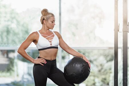 Beautiful sporty woman working out in gym using medicine ball