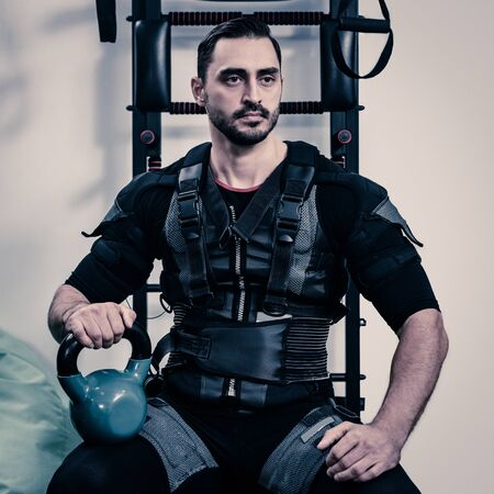 Portrait of young concentrated athletic man in EMS suit holding dumbbell Stok Fotoğraf