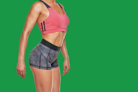 Closeup photo of strong shapely female body in sportswear isolated on green background
