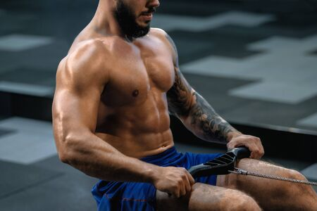 Young muscular man with tattoo doing exercises on rowing machine in gym