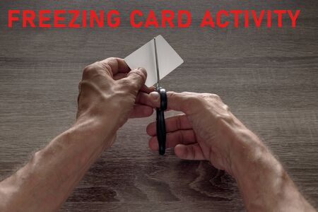 male hands with scissors cut the payment card. concept of liquidation, destruction of deactivation, decommissioning with the inscription freezing card activity.