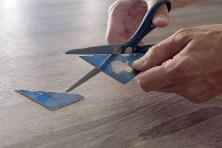 male hands with scissors cut the payment blue master card. concept of liquidation, destruction of deactivation, decommissioning
