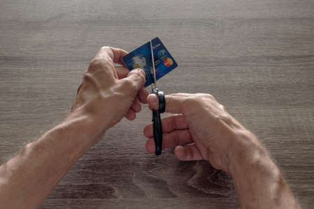 Dnepr, Ukraine- June 29, 2020: male hands with scissors cut the payoneer payment blue master card. concept of liquidation, destruction of deactivation, decommissioning 에디토리얼
