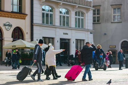 Krakow, Poland- February 07, 2020: Group of foreign tourists with luggage walking on city street