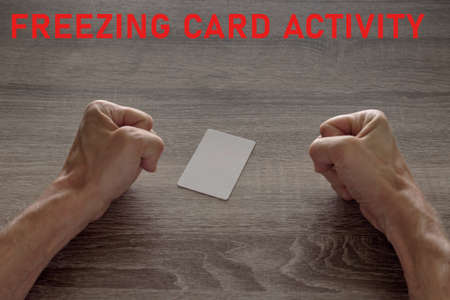 credit empty card and hands clenched into a fist. something went wrong with finances, concept with the words freezing card activity. 免版税图像