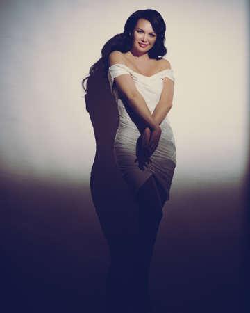 Sensual elegant brunette woman posing on wall background. retro style toned image