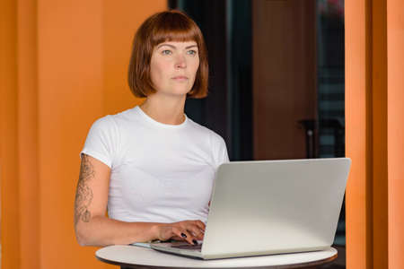 Young freelancer woman with laptop working on project in modern office