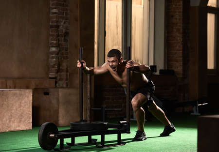 Strong healthy muscular sportsman pulling cross fit sled in gym