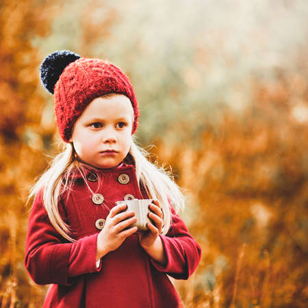 Portrait of cute little girl holding cup of tea in autumn park