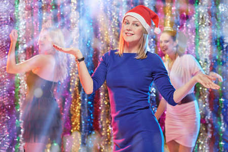 Attractive blonde in xmas cap dancing on New Year lights background
