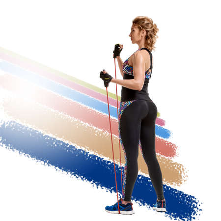 Strong fit slim woman using resistance band in her training on a white background with colorful stripes