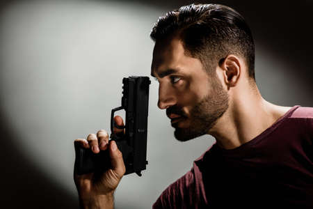 Closeup photo of young brutal special agent holding gun