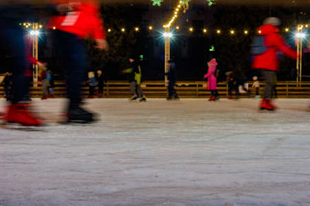 People skating on ice rink during winter festive evening