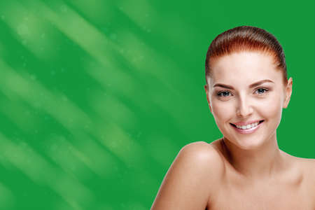 Studio portrait of young pretty woman with houlders and perfect skin on a green background with spots