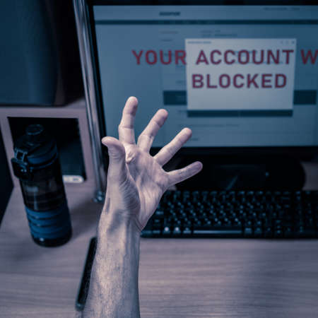 hand of Frustrated angry man showing middle finger to computer screen with text Your account was blocked.