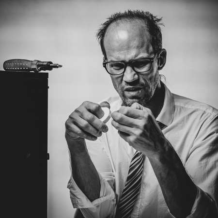 Black and white photo of Sad man applying band aid on finger after fixing broken computer in office